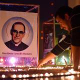 Un feligrés salvadoreño enciende velas ante la imagen de San Óscar Romero.