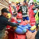 Una voluntaria carga a uno de los menores víctima del  fatal derrumbe de ayer.