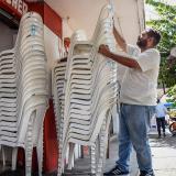 Andrés Sabatil acomoda la pila de sillas que va a alquilar en la 44 con 67.