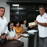 El contralor departamental del Atlántico, Carlos Rodríguez Navarro, hace entrega del cheque a Enrique Vengoechea, director de Indeportes Atlántico.