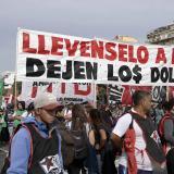 Manifestantes con carteles de protesta contra el mandatario Mauricio Macri.
