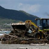 Una retroexcavadora retira troncos de la orilla de la playa en Miramar.