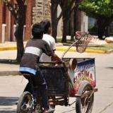 Dos menores de edad se transportan en un carricoche de venta de agua.