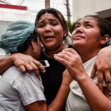 Tres mujeres se abrazan en las afueras de la Clínica La Merced mientras los rescatistas sacan a los pacientes internos.