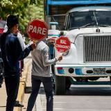 Dos estudiantes detienen a una tractomula para que las personas puedan cruzar por la calle.
