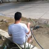 Un usuario con manguera en mano aguarda a que el agua llegue por las redes.