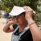 Una mujer se cubre del sol con una hoja de papel, mientras se hidrata con una bebida.