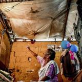 Magaly Fernández señala hacia las bolsas de plástico que la protegen del agua de lluvia en su habitación.