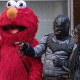 Una mujer posa con un hombre disfrazado de Batman y otras personas de Elmo.