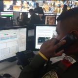 Un policía atiende una de las 1.475 llamadas que a diario se reciben a través de la línea 123.