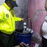 Momento en que oficiales de la Policía allanan una de las viviendas donde se fabricaba licor adulterado.