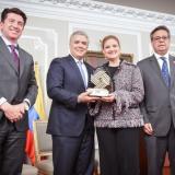 El presidente Iván Duque entregó el premio a la secretaria distrital de Desarrollo Económico, Madelaine Certain. Los acompaña Fernando Grillo, director de Función Pública.