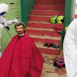 Habitante de la calle recibiendo servicio de barbería.