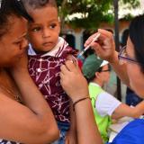 Una enfermera aplica una vacuna de un menor de edad.