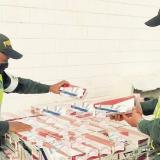Dos policías revisan el producto decomisado.