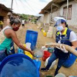 La secretaria General del Distrito, Diana Martínez, apoya a una ama de casa en la recolección de agua a través de un carrotanque.