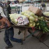 Un hombre hala una carreta con alimentos este martes en una plaza de mercado en Cali.