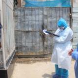 Dos funcionarios de salud hablan con una ciudadana de Cartagena en cumplimiento de la vigilancia epidemiológica en la actual pandemia.