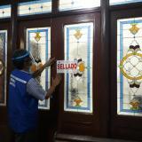 Un hombre pone el sello en la puerta principal de la funeraria.