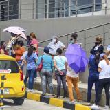 Un grupo de personas realizan una fila a las afueras de un local.