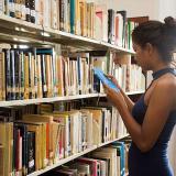 Una mujer mira la cubierta de un libro entre los anaqueles de la Biblioteca Piloto del Caribe.