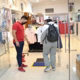 Un trabajador de un local comercial da instrucciones a un cliente.