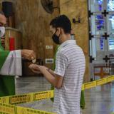 Monseñor Pablo Emiro Salas entrega la hostia a un feligrés en las manos durante el ritual de la comunión.