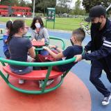 Un grupo de niños, protegidos por mascarillas, juega en el Parque Simón Bolívar de Bogotá.