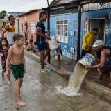 Un grupo de jóvenes sacan agua de una vivienda luego de que el Arroyo Hospital se desbordara.
