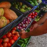 Una persona escoge verduras en un mercado.