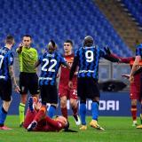 Jugadores de ambos equipos protestan al juez tras una falta sobre un futbolista romano.