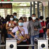 Un grupo de personas camina en el interior de una estación de Transmetro.