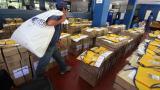 Un empleado de Correos carga urnas electorales para ser repartidas en los colegios de votación en la localidad de Resistencia, provincia de Chaco.