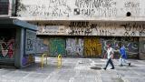 Varios ciudadanos caminan por una céntrica calle de Sao Paulo. Al fondo, uno de los grafitis que será borrado por la Alcaldía.