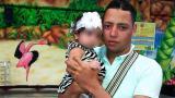 Jhoan Rodríguez Vega carga a su pequeña de dos años.