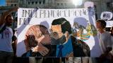 Ciudadanos sostienen un pasacalle con un dibujo que muestra al jefe del gobierno español, Mariano Rajoy dándose un beso con el presidente catalán, Carlos Puigdemont.