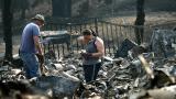 Un hombre se limpia los ojos mientras mira los restos de su casa.
