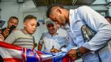 Miguel Ángel Borja, junto a Alejandro Char, firmándole una bandera del Junior a un pequeño que lo abordó en el aeropuerto.