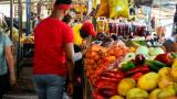 Los compradores se acercan a los puestos de frutas y verduras en el mercado de la ciudad.