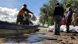 Comunidad y personal de organismos de socorro ponen los sacos rellenos de arena.