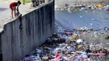 Una mujer arroja desechos al cauce del arroyo de Rebolo, ubicado en el suroriente de la ciudad.