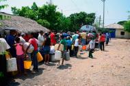 Un grupo de personas hace fila para recibir agua de un carrotanque, en Bosconia.