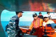 Oficiales de la Armada indonesia y los equipos de rescate en busca de las víctimas del avión de la policía se estrelló en las aguas de Senayang, Islas Riau.