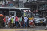 Un grupo de ciudadanos circula por el Centro de Barranquilla mientras cae la lluvia.