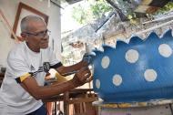El artista Gustavo Laurens ultimando los detalles de una matera hecha en llantas.