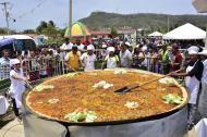 Personas revisan la paella gigante durante su cocción.