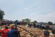 Los escombros del edificio desplomado son retirados por los grupos de rescate.