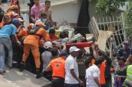 Miembros de la Defensa Civil evacuan a uno de los sobrevivientes del derrumbe del edificio.
