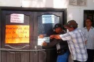Trabajadores y extrabajadores ponen carteles frente a la Alcaldía.