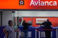 Antony Cárdenas (c) intenta conseguir un tiquete para viajar por Avianca.